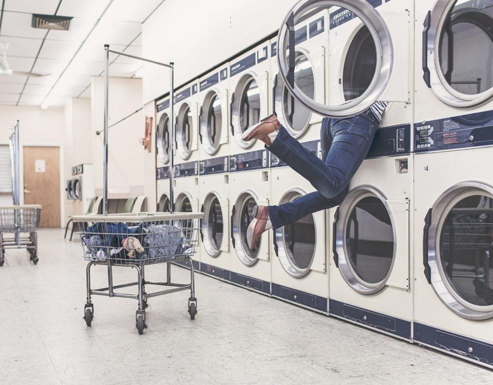 zdjęcie pralni z mężczyzną z głową w pralce